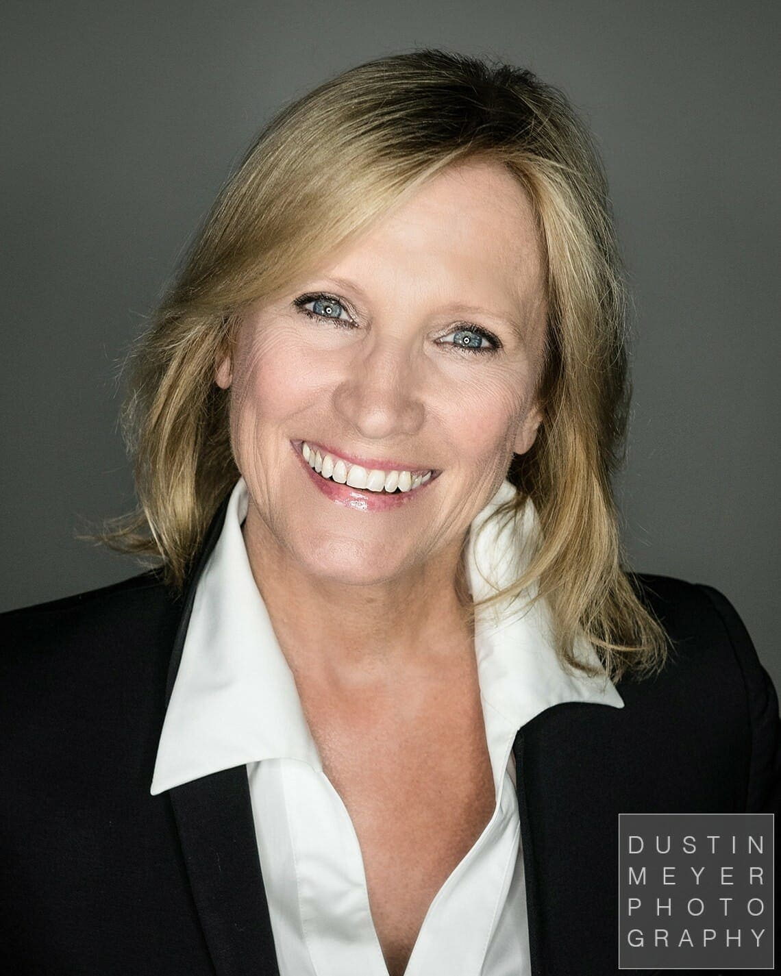 professional headshot tips a blonde woman in a black business jacket and white shirt