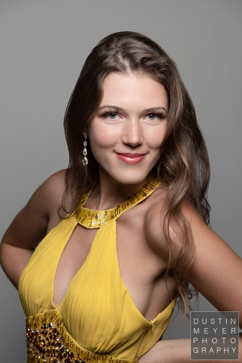 A brunette female model in a professional photography studio wearing a yellow dress in front of a white backdrop indoors