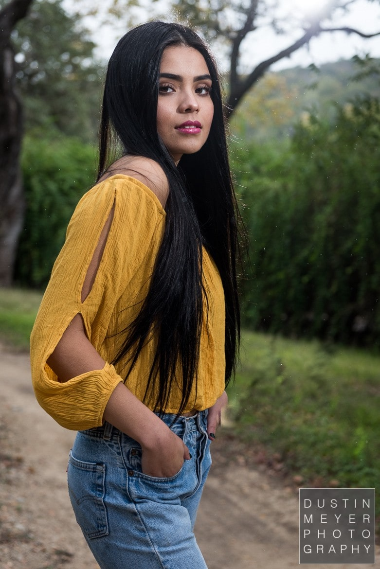 a female model with black hair outdoors wearing a yellow shirt and jeans