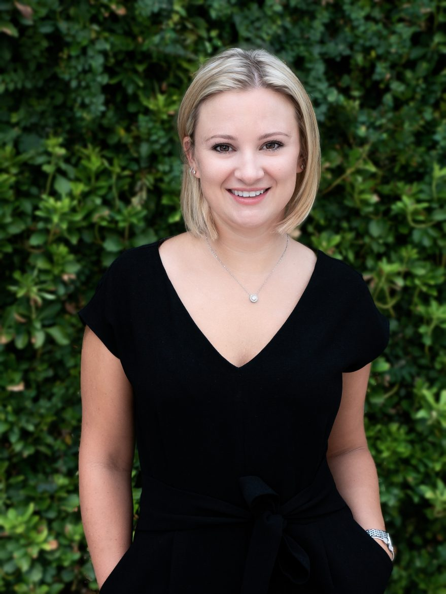 Outdoor headshot of a blonde female girl woman wearing a black shirt standing in front of a wall with green vines at the Domain Austin