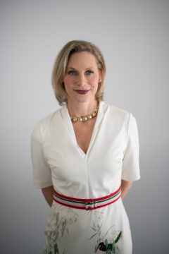A professional company headshot of a blonde woman wearing a white dress in front of a white background with natural light.